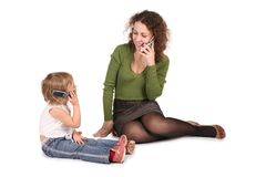 Mother and daughter talk on the cell. Mother and daughter sitting they talk on the cell phones on the the white Royalty Free Stock Photo