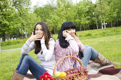 Mother and daughter talk on the phone in the park Stock Image