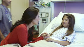 Mother And Daughter Talking With Male Nurse in Hospital Room