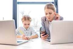 Mother and daughter talking while sitting at table with laptops Stock Images