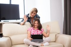 Mother and daughter talking with somebody other video call on a tablet PC. In the living room Royalty Free Stock Photos