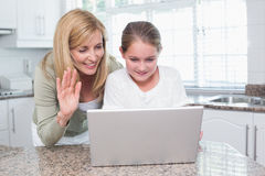 Mother and daughter talking with someone with the laptop Royalty Free Stock Photos