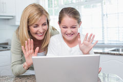 Mother and daughter talking with someone with the laptop Stock Photo