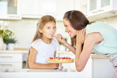 Mother and daughter tasting fruitcake Stock Photo