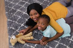 Mother and daughter with teddy bear while lying on rug at home Royalty Free Stock Image
