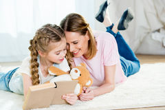 Mother and daughter with teddy bear reading book on carpet Royalty Free Stock Photo