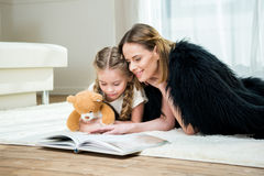 Mother and daughter with teddy bear reading book on carpet Stock Images