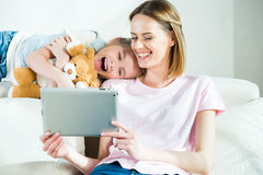 Mother and daughter with teddy bear using digital tablet at home Stock Image