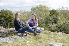Mother and Daughter. Mother and teenage daughter sitting down, chatting and smiling during a hillside walk, relaxing together. Outdoors lifestyle royalty free stock photography