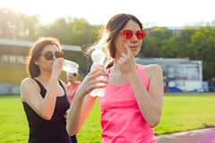 Mother and daughter teenager resting after workout at stadium, drink water Royalty Free Stock Image