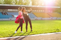 Mother and daughter teenager resting after workout at stadium. Photographed together selfi photo. Royalty Free Stock Photos