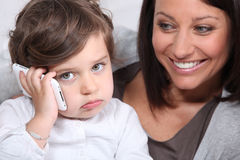 Mother and daughter with telephone Stock Images