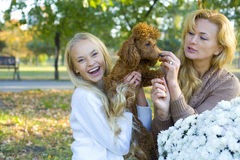 Mother, daughter and their dog poodle in a park in autumn. Happy mother and daughter walking with his dog in the park Stock Image
