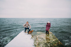 Mother and daughter with their little pet dog walking on the old pier. Winter holidays, sea background Stock Photos