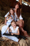 Mother and daughter. Three beautiful girl with long healthy hair in hats sitting on hayloft in cowboy clothes on a horse farm royalty free stock photography