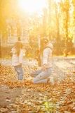 Mother and daughter throw up fallen leaves. Joy. royalty free stock image