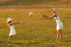Mother and daughter throwing ball to each other Stock Photo