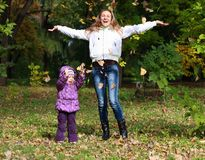 Mother and Daughter Throwing Dry Leaves in Autumn Stock Photos