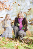 Mother and daughter throwing leaves in the air Stock Photos