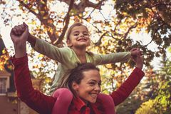 Mother daughter time, Mother carrying girl on piggyback. stock images