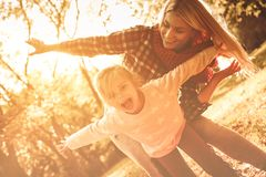 Mother daughter time. Cheerful single mother with open arms playing with daughter in park stock photos