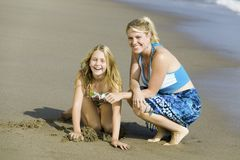 Mother and Daughter Together on Beach Stock Images