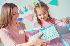 Mother and daughter together celebration at home sitting on sofa girl opening present. Young mother and little daughter celebration together at home sitting on Royalty Free Stock Photos