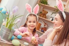 Mother and daughter together easter preparation at home sitting in bunny ears girl coloring eggs Royalty Free Stock Photo
