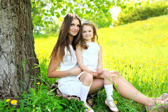 Mother and daughter together on the grass near tree in summer Stock Photography