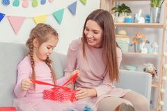 Mother and daughter together at home celebration concept sitting girl opening present box. Young mother and little daughter together at home celebration concept Stock Photos
