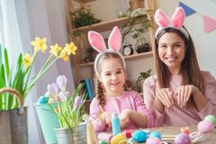 Mother and daughter together at home easter preparation in bunny ears rabbit pose stock photo