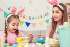 Mother and daughter together at home easter preparation in bunny ears sitting coloring eggs in water excited Stock Images