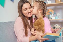 Mother and daughter together at home woman reading book to girl royalty free stock images