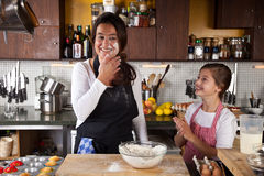 Mother and Daughter together in kitchen Stock Photo