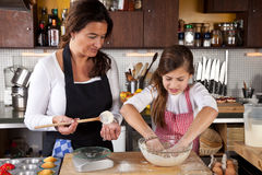 Mother and Daughter together in kitchen stock photos