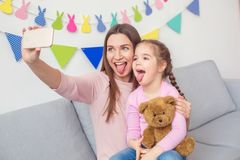 Mother and daughter together weekend at home sitting taking selfie photos on smartphone royalty free stock image