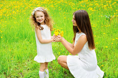 Mother and daughter together with yellow dandelion flowers Royalty Free Stock Photos