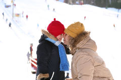 Mother and daughter touching noses. Mother daughter noses together and warming in ski resort Royalty Free Stock Images
