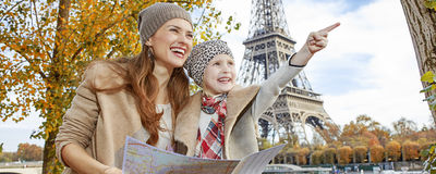 Mother and daughter tourists in Paris holding map and pointing Stock Images