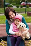 Mother and daughter with toy dog at bench Stock Images