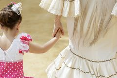 Mother and daughter in traditional dress taking a walk and enjoying at the Seville`s April Fair.  royalty free stock photography