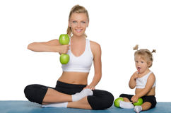 Mother with daughter train weights of apples Stock Images