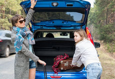 Mother and daughter traveling by car with suitcases. Royalty Free Stock Photography
