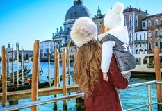 Mother and daughter travellers in Venice having excursion. Another world vacation. Seen from behind modern mother and daughter travellers on embankment in Venice Royalty Free Stock Photography