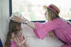Mother and daughter travels in the train - woman helps wearing hat for girl stock images