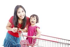Mother with daughter on trolley. Portrait of smiling mother with her daughter in the shopping cart Royalty Free Stock Images
