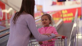 Mother with daughter in trolley riding escalator to next floor at supermarket. Young mother with little cute daughter in trolley riding escalator to next floor stock footage