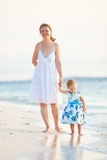 Mother and daughter on tropical beach at sunset Stock Photos