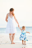 Mother and daughter on tropical beach at sunset Stock Images