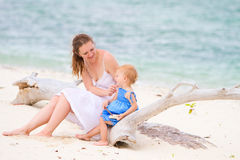 Mother and daughter on tropical white sand beach Stock Photography